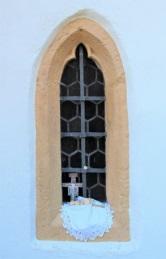 Sakristeifenster der Ober-Beerbacher Kirche mit Kruzifix und Hostie
